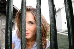 Menina que olha através da cerca Imagens de Stock Royalty Free