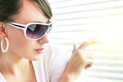 Menina que olha através das cortinas imagem de stock royalty free