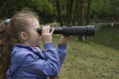 Menina que olha através de um telescópio Fotografia de Stock