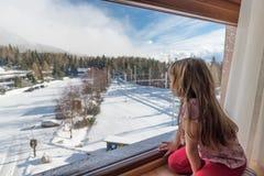 Menina que olha através de uma janela no dia de inverno Fotos de Stock Royalty Free