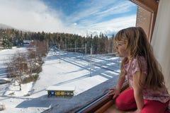 Menina que olha através de uma janela no dia de inverno Imagem de Stock Royalty Free
