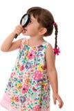 Menina que olha através de uma lupa fotografia de stock