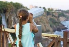 Menina que olha através dos binóculos ao mar Mediterrâneo fotografia de stock