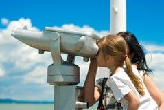 A menina que olha através pagar-à-usa o telescópio Imagens de Stock