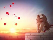 Menina que olha balões vermelhos Fotografia de Stock Royalty Free