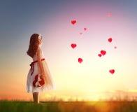 Menina que olha balões vermelhos Fotos de Stock Royalty Free