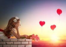 Menina que olha balões vermelhos Fotografia de Stock