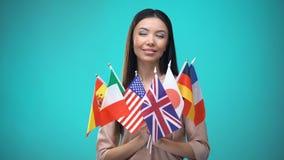 Menina que olha bandeiras em suas mãos, programa internacional da troca do estudante vídeos de arquivo