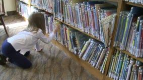 Menina que olha com as fileiras dos livros de crianças (1 de 4) video estoque
