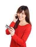Menina que olha com o cartão de crédito no telefone celular Fotografia de Stock