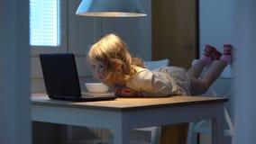 Menina que olha entusiasticamente desenhos animados no portátil que encontra-se na tabela vídeos de arquivo