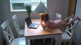 Menina que olha entusiasticamente desenhos animados no portátil que encontra-se na tabela video estoque