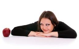 Menina que olha fixamente na maçã vermelha Imagem de Stock Royalty Free