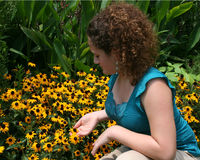 Menina que olha flores imagem de stock royalty free