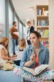 Menina que olha fora na biblioteca de faculdade Fotos de Stock