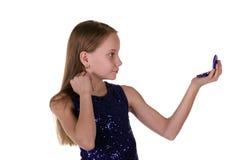 Menina que olha no espelho imagem de stock