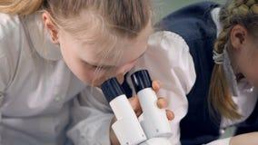 A menina que olha no microscópio que faz a experiência da ciência Close-up 4K vídeos de arquivo