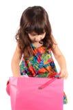 Menina que olha no saco do presente Imagem de Stock Royalty Free