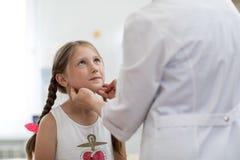 Menina que olha o doutor que que testa suas amídalas Fotos de Stock