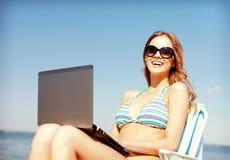 Menina que olha o PC da tabuleta na praia Fotos de Stock Royalty Free