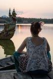 Menina que olha o por do sol e que medita em Kanchanaburi, Thailan Imagem de Stock