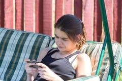 Menina que olha o telefone Fotos de Stock