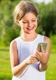 Menina que olha o telefone móvel fotos de stock