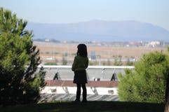 Menina que olha para fora através da vista Fotografia de Stock Royalty Free