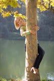 A menina que olha para fora devido a uma árvore Imagens de Stock Royalty Free