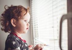 Menina que olha para fora a janela Foto de Stock Royalty Free