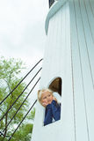 Menina que olha para fora a janela da torre Fotografia de Stock