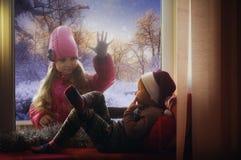 Menina que olha para fora a janela em uma noite do inverno fora Fotografia de Stock Royalty Free