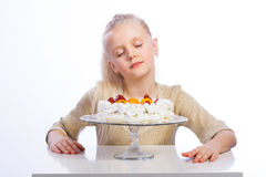 Menina que olha queques do chocolate Foto de Stock Royalty Free