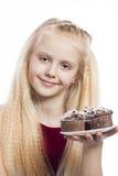 Menina que olha queques do chocolate Imagens de Stock Royalty Free