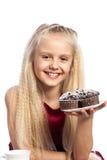 Menina que olha queques do chocolate Fotografia de Stock Royalty Free