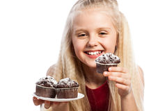 Menina que olha queques do chocolate Fotos de Stock