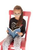 Menina que olha sobre os vidros nerdy que leem um livro Imagens de Stock