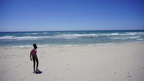 Menina que olha sua sombra que anda ao longo do mar bonito Fotografia de Stock Royalty Free