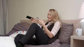 Menina que olha a tevê, ao usar o smartphone na cama Imagem de Stock Royalty Free