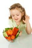 Menina que olha uma bacia de vegetais fotos de stock royalty free