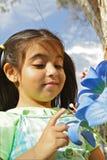 Menina que olha uma flor azul Fotografia de Stock