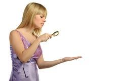 A menina que olha uma mão através de um magnifier fotos de stock