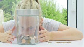 Menina que põe moedas em um frasco video estoque