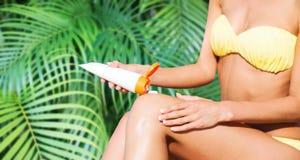 Menina que põe o creme da proteção do sol sobre a cadeira de praia Imagem de Stock Royalty Free