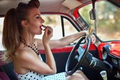 Menina que põe sobre o batom ao conduzir Fotografia de Stock Royalty Free