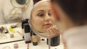 Menina que põe sobre o batom que olha no espelho, close up vídeos de arquivo