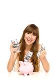 Menina que põr o dinheiro no banco piggy foto de stock