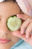 Menina que põr o pepino cortado sobre seu olho Fotografia de Stock