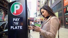 Menina que paga estacionar no medidor de estacionamento vídeos de arquivo
