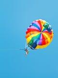 Menina que parakiting no paraquedas no céu azul Imagem de Stock Royalty Free